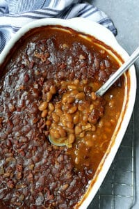 Kicked Up Canned Baked Beans - Overhead shot of the baked beans in white baking dish