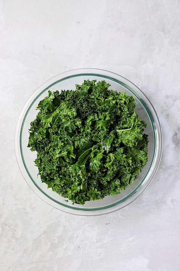 Overhead shot of massaged kale in glass bowl