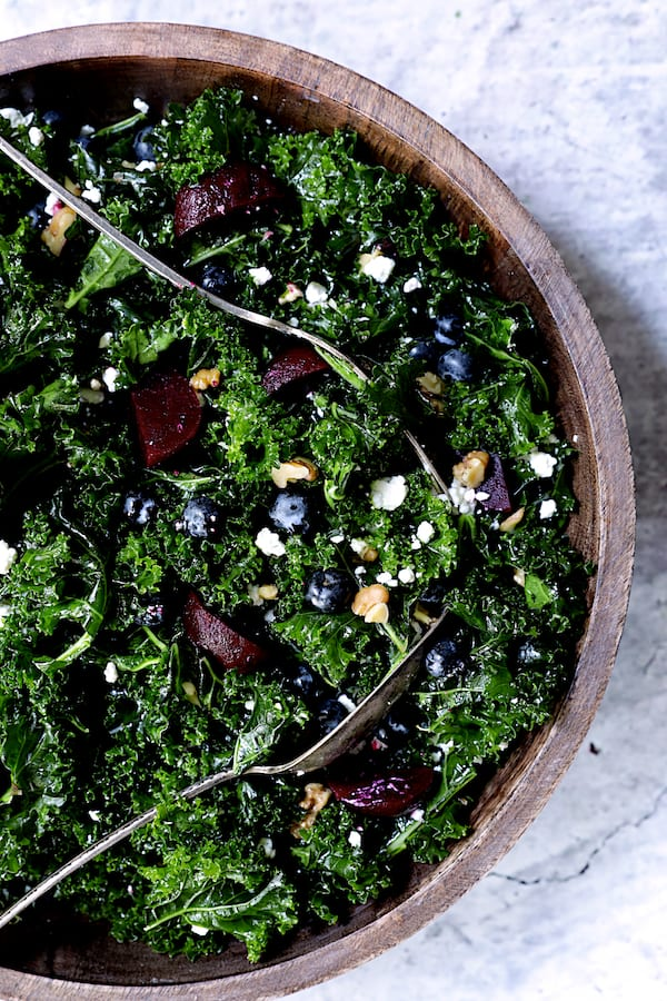 Photo of Massaged Kale, Beet and Blueberry Salad with Honey - Balsamic Dressing being tossed with serving utensils.
