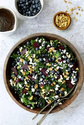 Massaged Kale, Beet and Blueberry Salad with Honey - Balsamic Dressing - Overhead hero shot of salad in wood bowl on gray stone background
