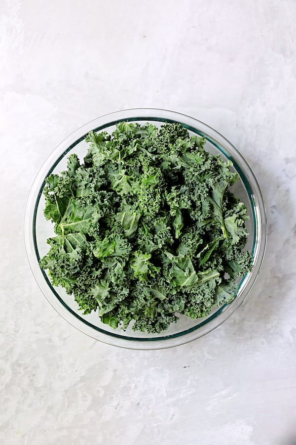 Overhead shot of fresh kale in glass bowl