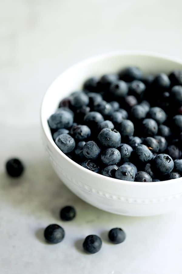 Straight-on shot of fresh blueberries in white bowl