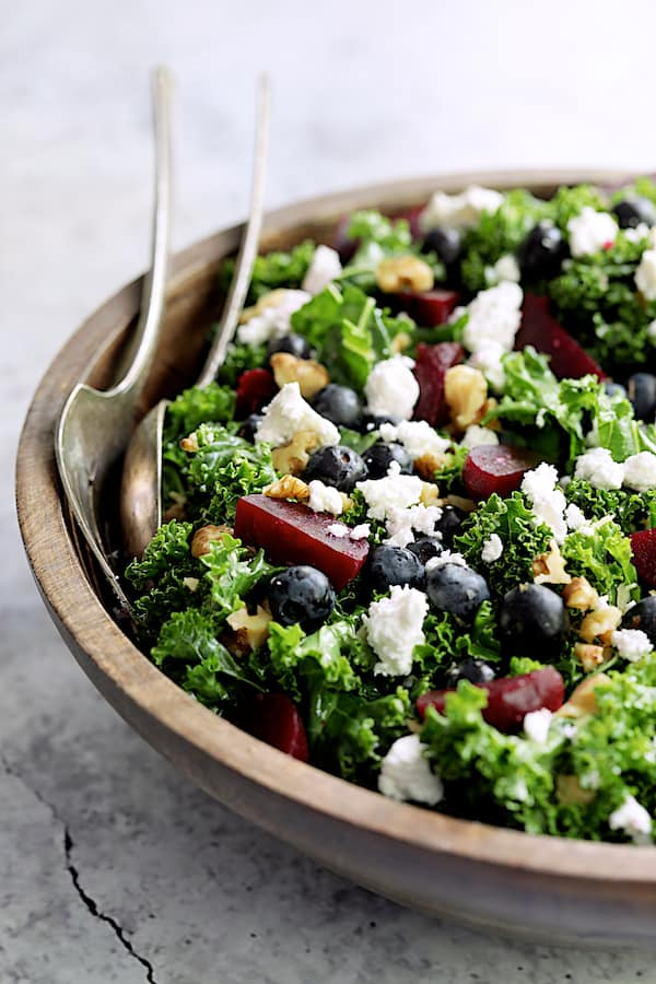 Close-up photo of Massaged Kale, Beet and Blueberry Salad with Honey - Balsamic Dressing assembled in wood bowl.