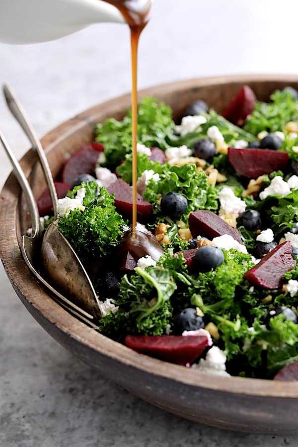Massaged Kale, Beet and Blueberry Salad with Honey - Balsamic Dressing - Close-up shot of dressing being drizzled onto salad