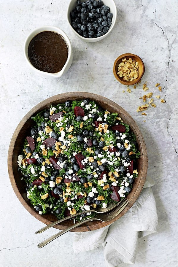 Photo of Massaged Kale, Beet and Blueberry Salad with Honey - Balsamic Dressing with dressing, blueberries and walnuts in small bowls on stone background.