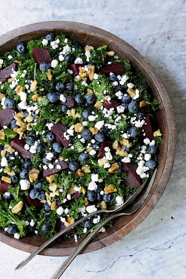 Massaged Kale, Beet and Blueberry Salad with Honey - Balsamic Dressing - Overhead close-up shot of salad in wood bowl with serving utensils