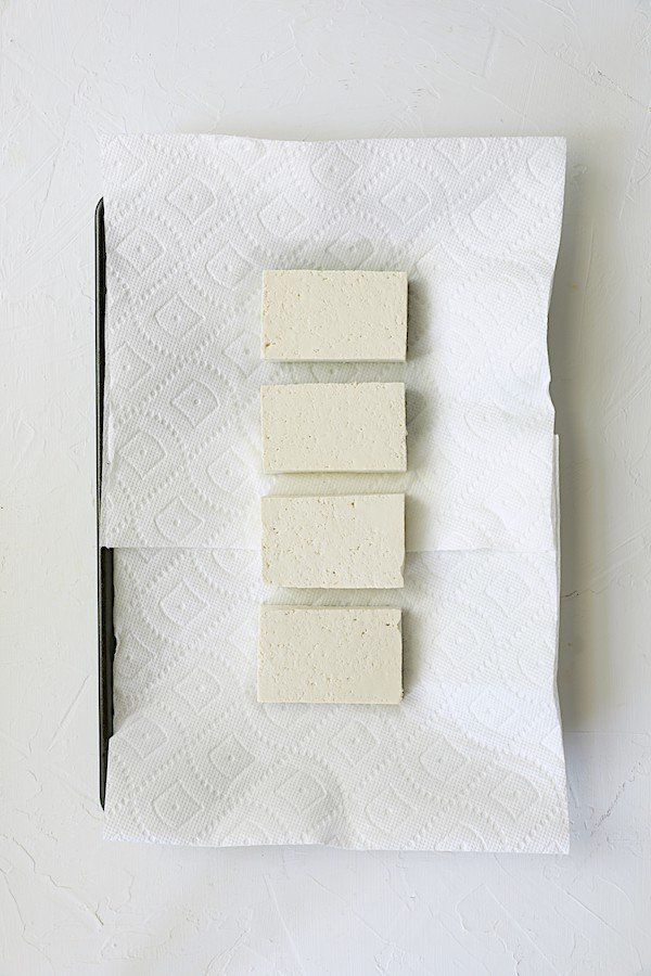 Photo of four pieces of tofu being drained on paper towels.