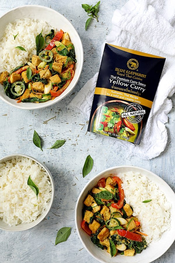 Thai Yellow Curry with Crispy Tofu and Vegetables - Overhead shot of two bowls of the curry and rice with curry sauce packaging