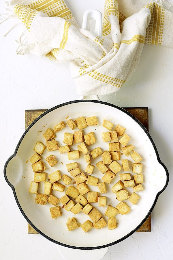 Photo of tofu being browned in white enameled skillet.