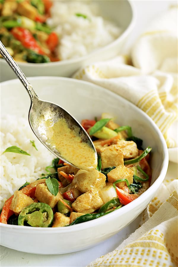 Thai Yellow Curry with Crispy Tofu and Vegetables - Straight-on close-up shot of curry with sauce being drizzled over