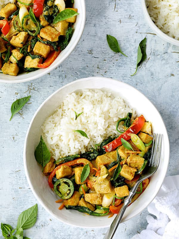 Thai Yellow Curry with Crispy Tofu and Vegetables - Overhead hero shot of dish in white bowls garnished with Thai basil