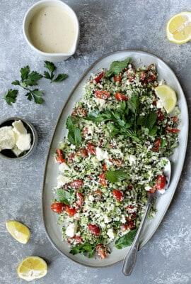 Cauliflower Tabouli with Lemon Tahini Dressing and Feta Cheese - Overhead hero shot of salad on large oval platter garnished with parsley and lemons