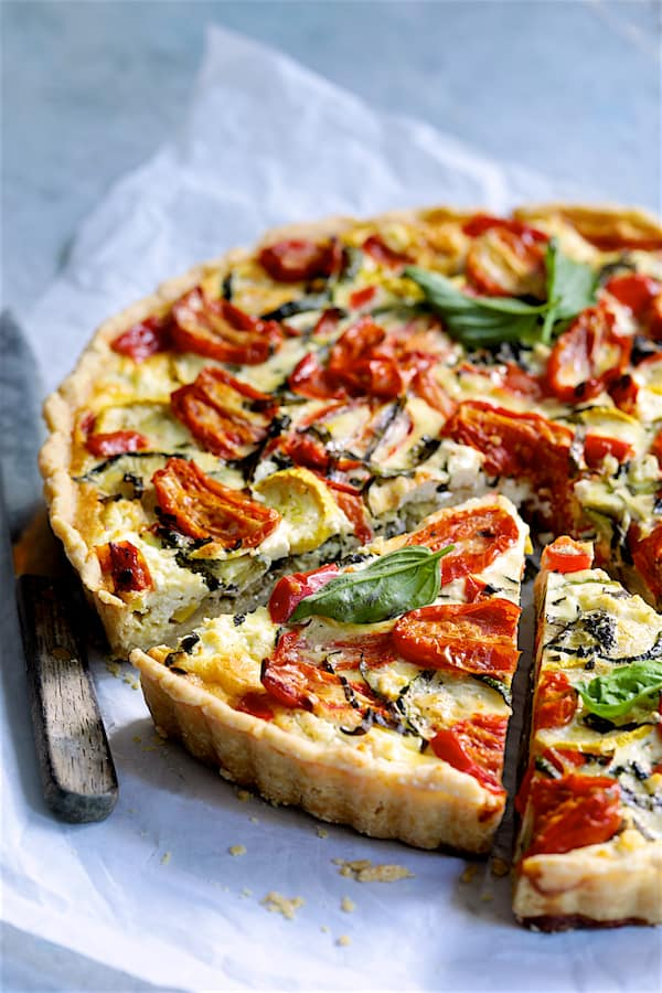 Provencal Vegetable and Goat Cheese Tart - Close-up shot of tart slices on white parchment paper with knife
