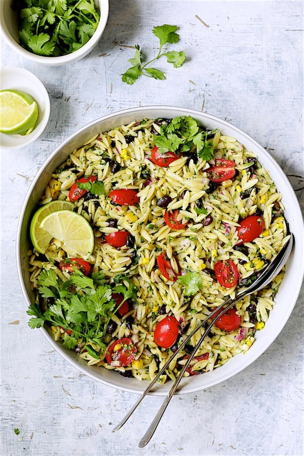 Southwestern Orzo Salad with Cilantro Lime Dressing - Overhead shot of salad in serving bowl garnished with lime wedges and cilantro