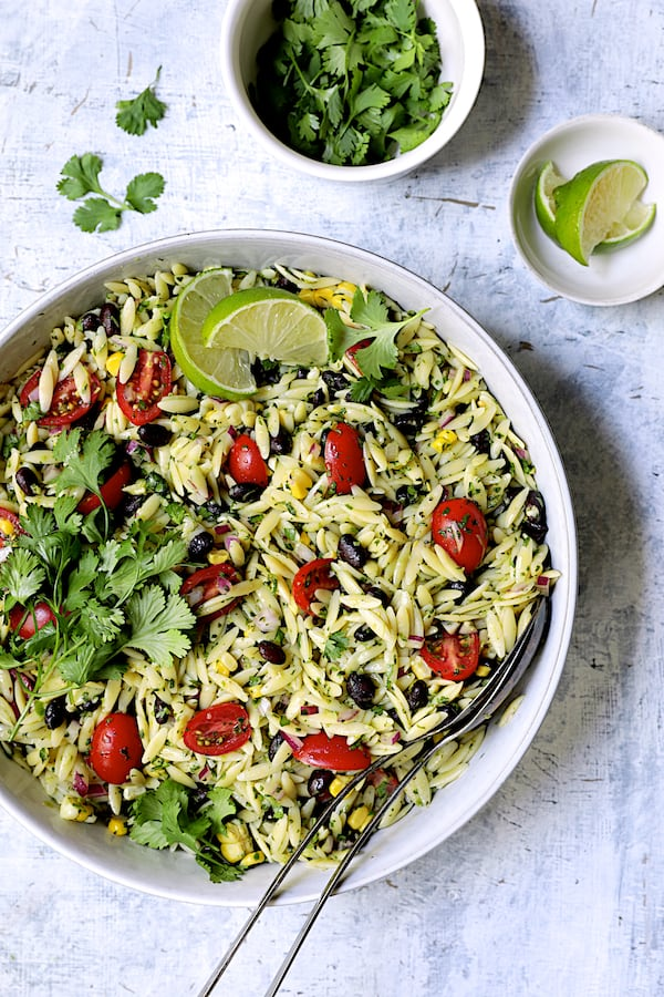 Southwestern Orzo Salad with Cilantro Lime Dressing - Overhead shot of salad in white serving bowl garnshed with cilantro and lime