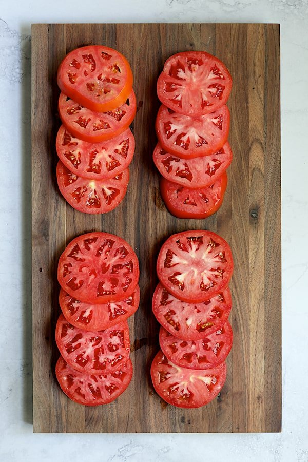 Overhead shot of 16 tomato slices on wood cutting board