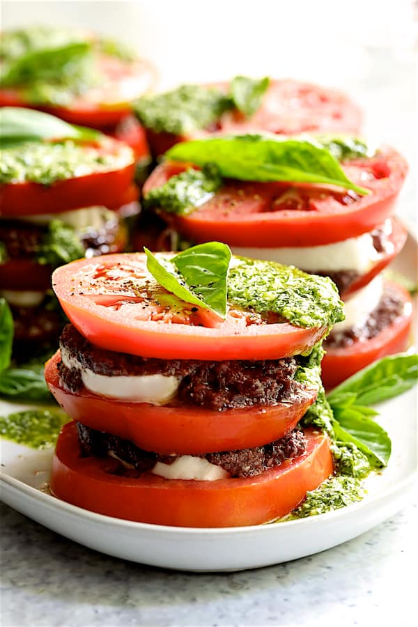Stacked Tomato Salad with Tapenade and Basil Pesto Dressing - Straight-on close-up shot of finished tomato stacks on white platter