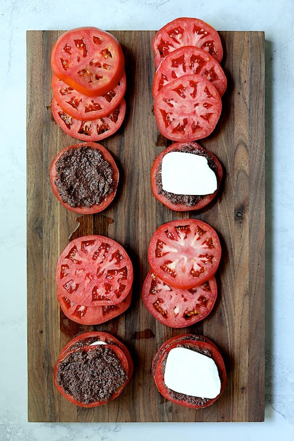 Overhead shot of tomato slices on wood cutting board being layered with tapenade and fresh mozzarella