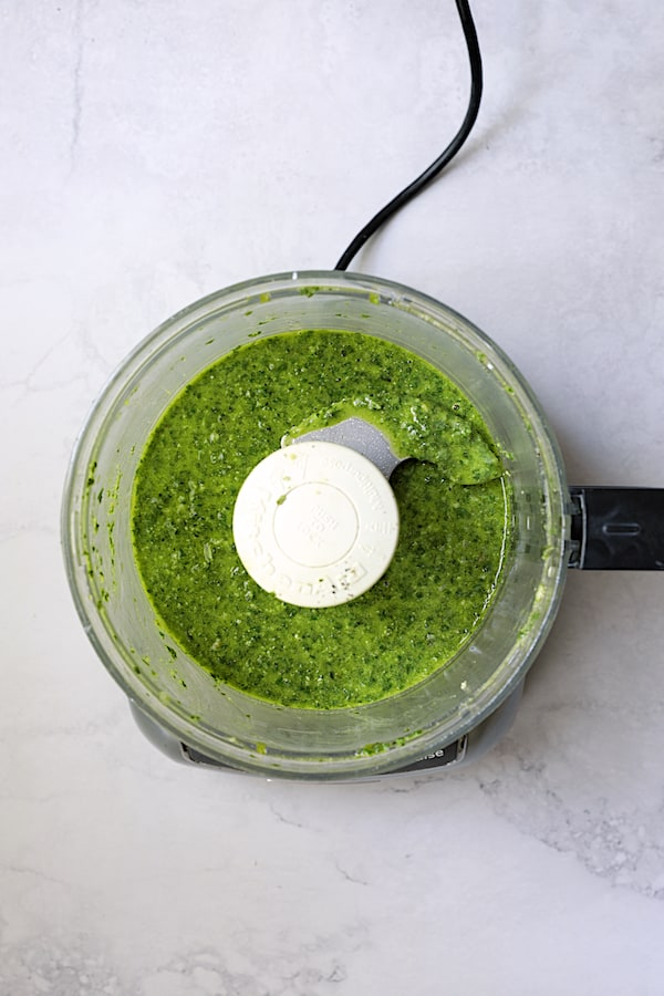 Overhead shot of basil pesto dressing in food processor