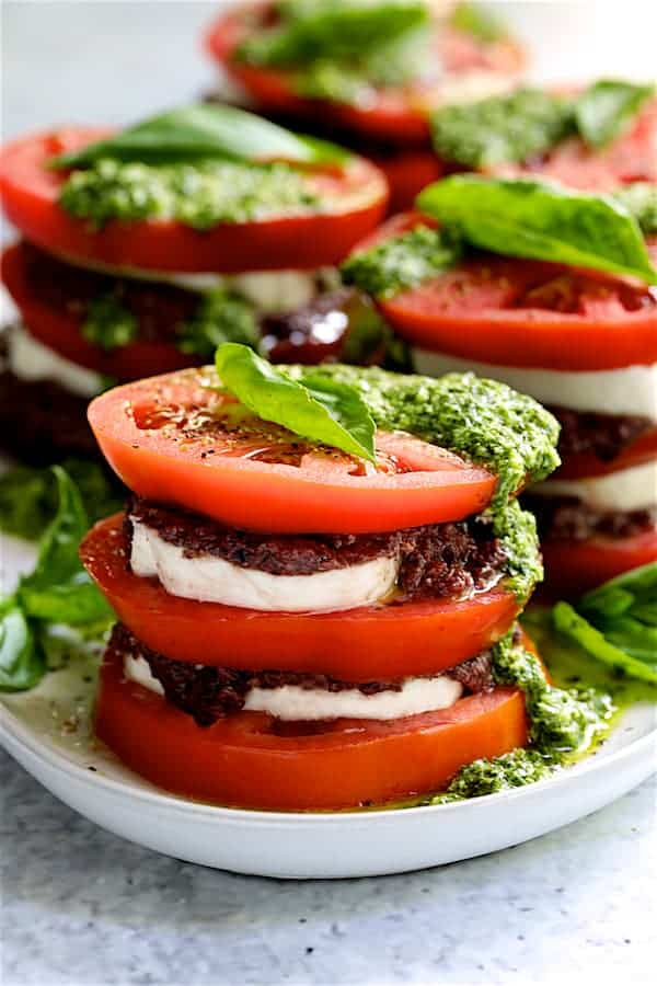 Photo of Stacked Tomato Salad with Tapenade and Basil Pesto Dressing on white platter.
