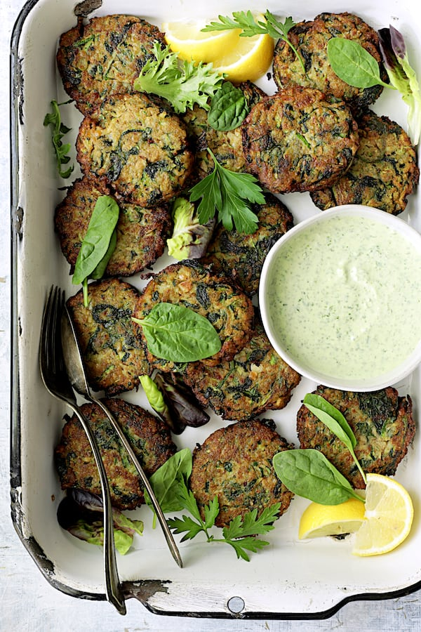 Zucchini Red Lentil and Spinach Fritters with Cilantro Yogurt Sauce - Overhead hero shot of fritters in white pan