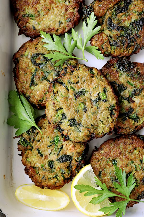 Zucchini Red Lentil and Spinach Fritters with Cilantro Yogurt Sauce - Overhead close-up shot garnished with fresh greens and lemon wedges