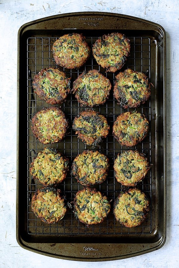 Overhead shot of fried zucchini fritters on rack over baking sheet