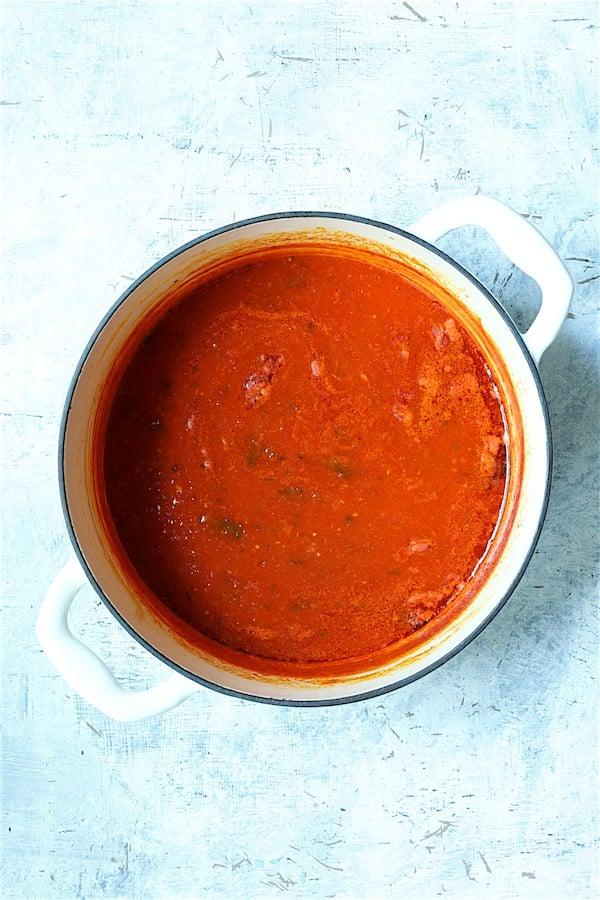 Overhead shot of tomato sauce in white Dutch oven