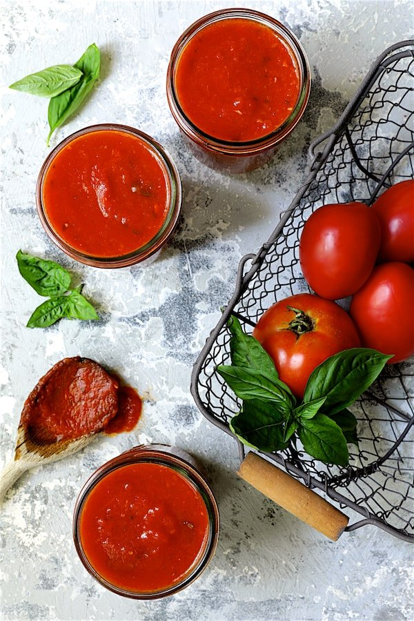 Basic Fresh Tomato Sauce (Parma Style) - Overhead shot of sauce in glass pint jars with tomatoes in wire basket