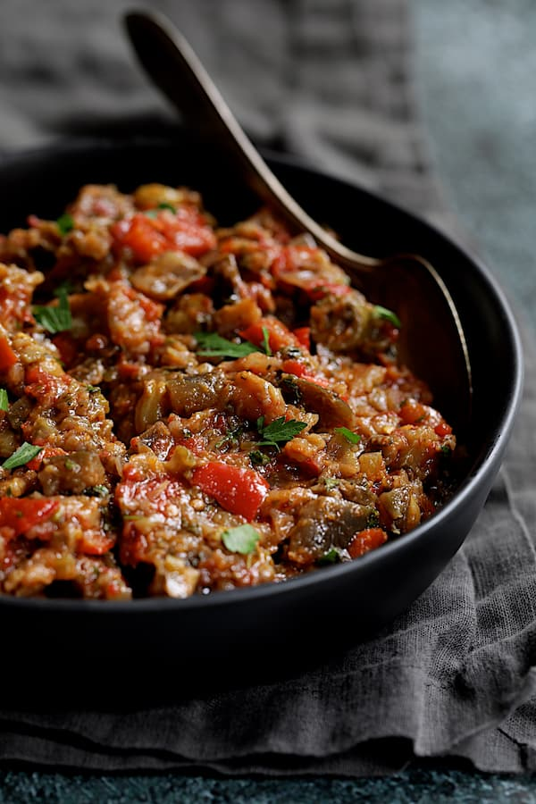 Close-up photo of Moroccan-Spiced Caponata in black serving bowl with spoon.