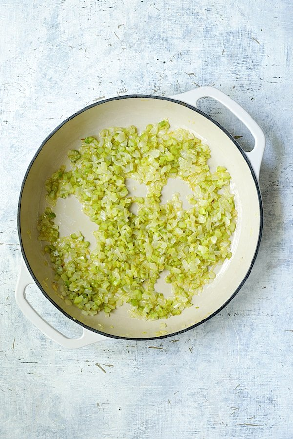 Onion and celery being cooked in white cast iron skillet