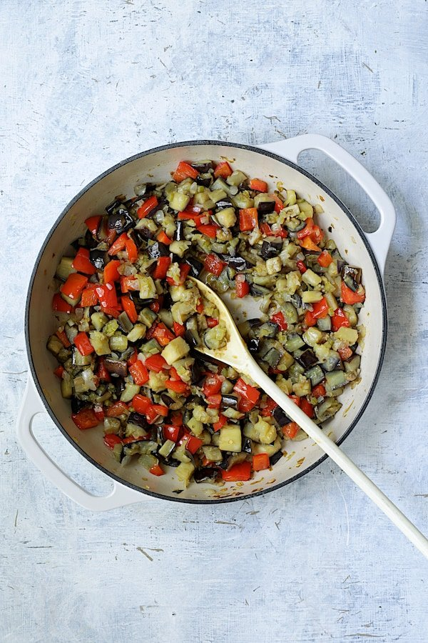 Photo of fresh ingredients for caponata being cooked in white cast iron skillet.