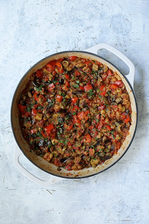 Photo of finished caponata in white cast iron skillet.