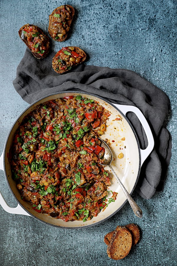 Photo of Moroccan-Spiced Caponata being served up on crusty bread from white cast iron skillet.