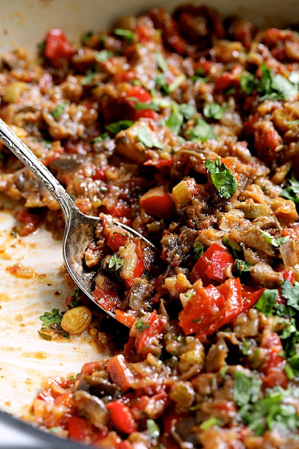 Close-up photo of finished Moroccan-Spiced Caponata with serving spoon.
