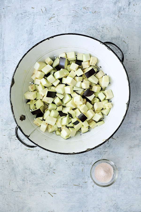 Cubed eggplant in white distressed colander with salt