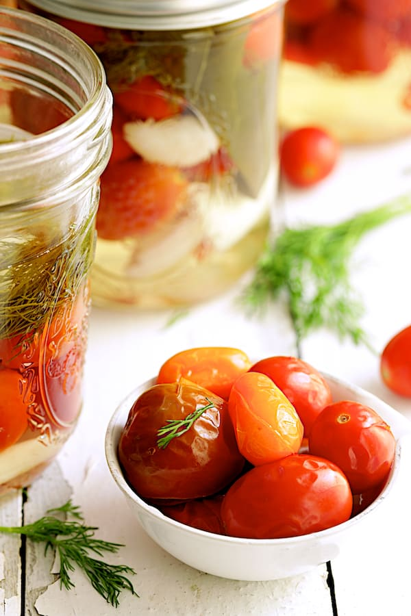 Pickled Grape Tomatoes - Close-up shot of pickled tomatoes in small white bowl garnished with dill