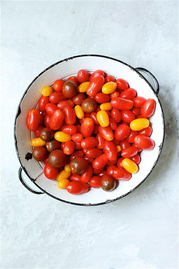 Overhead shot of grape tomatoes in white antique colander on white background.