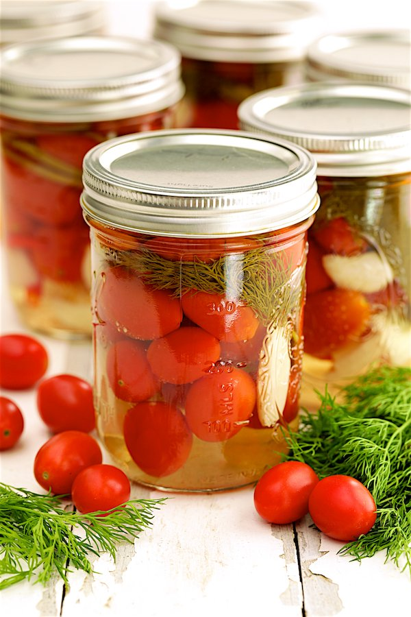 Pickled Grape Tomatoes - Hero shot of tomatoes in glass pint jar with fresh tomatoes and dill scattered around.