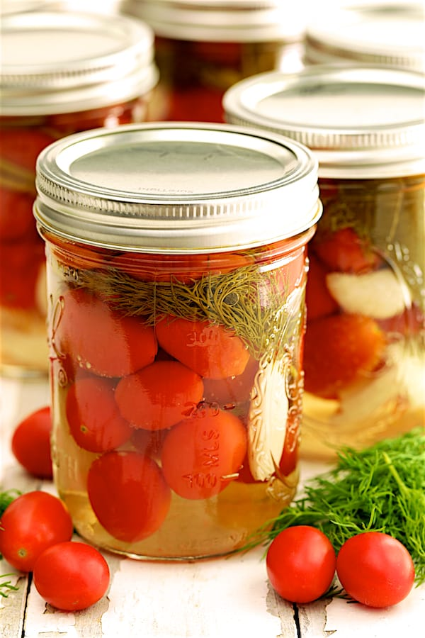 Pickled Grape Tomatoes - Close-up shot of finished tomatoes in glass pint jar with fresh dill and tomatoes scattered about
