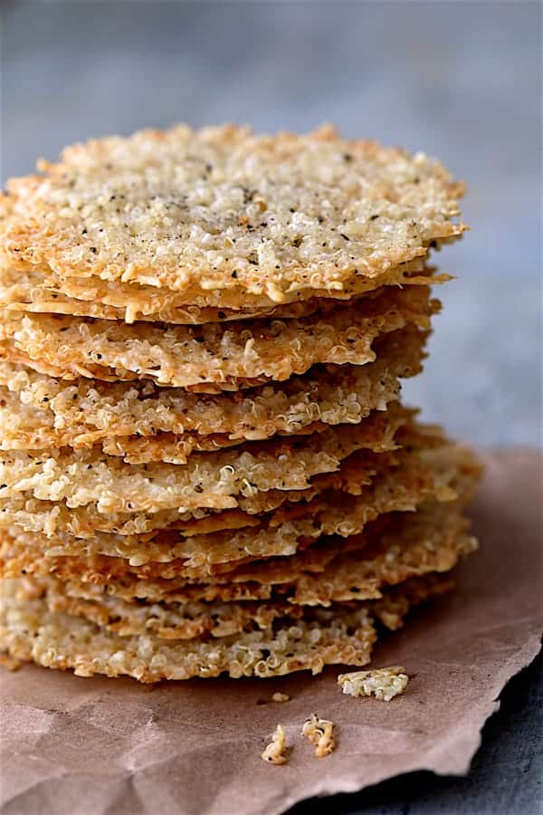 Quinoa Parmesan Crisps - Close up shot of a tall stack of the crisps on brown wrapping paper