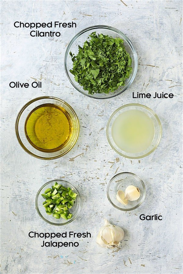 Overhead shot of ingredients for cilantro lime salad dressing in glass bowls