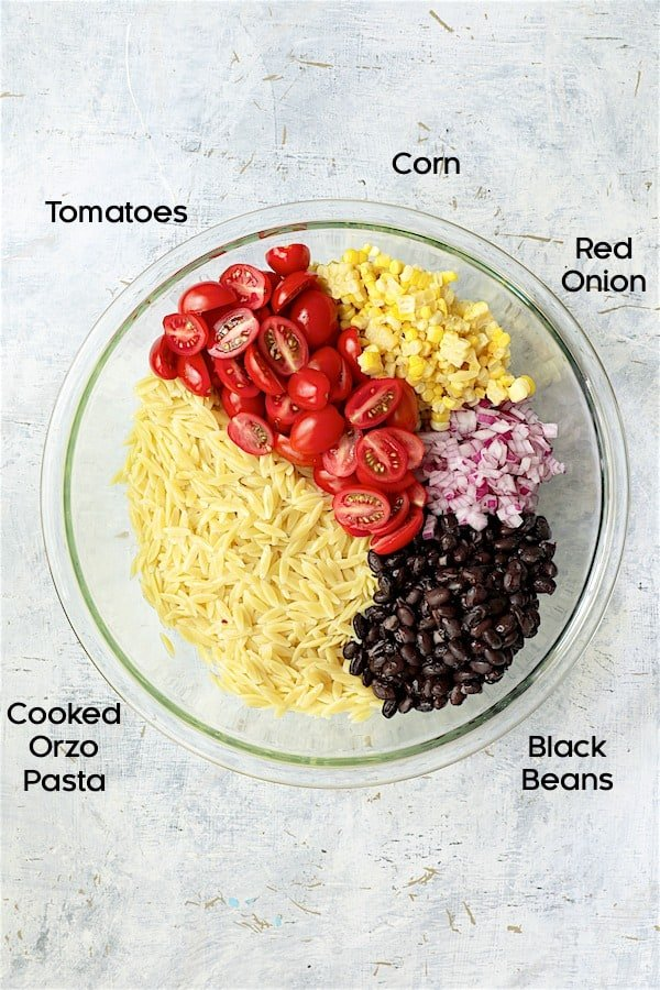 Overhead shot of ingredients for salad in glass bowl
