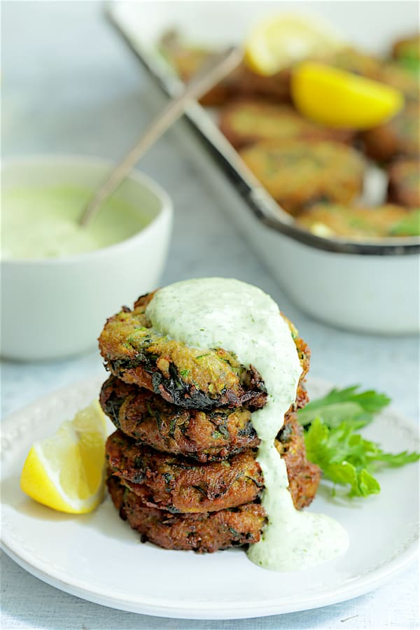 Zucchini Red Lentil and Spinach Fritters with Cilantro Yogurt Sauce - Four fritters stacked on white plate with sauce dripping down