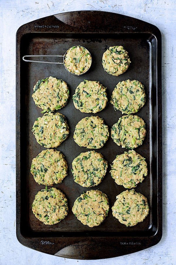 Photo of Zucchini, Red Lentil and Spinach Fritters on black baking sheet being being fried.