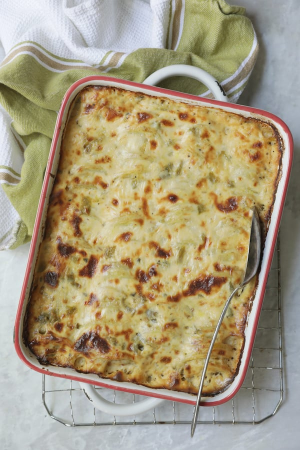 Photo of baked Au Gratin Potatoes with Green Chiles in white baking dish on cooling rack with green striped towel.