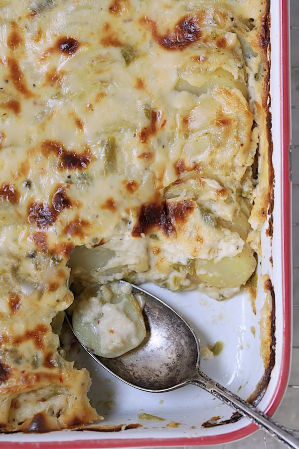 Au Gratin Potatoes with Green Chiles - Close-up shot of potatoes being spooned out of pan