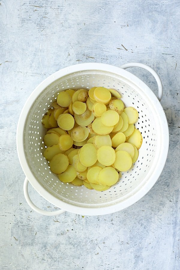 Photo of cooked potato slices in white colander.