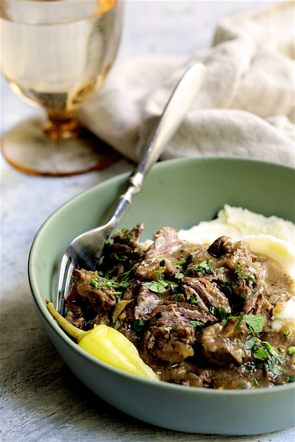 Photo of Mississippi-Style Boneless Short Ribs in green bowl with mashed potatoes garnished with parsley.