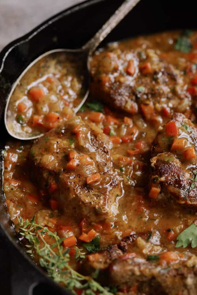 Cajun-Smothered Pork Medallions - Straight-on close-up shot in cast iron skillet